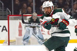 FILE - In this Saturday, March 7, 2020, file photo, Minnesota Wild defenseman Matt Dumba passes the puck during the first period of an NHL hockey game against the Los Angeles Kings in Los Angeles. Bonding between veterans and youngsters has been a time-honored tradition in hockey. But in yet another setback related to the relentless COVID-19, NHL protocols aiming to curb the virus spread and keep the schedule on track could make that vital off-ice development of camaraderie more difficult. (AP Photo/Mark J. Terrill, File)