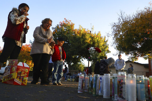 FILE - In this Nov. 24, 2019, file photo, community members gather at a memorial site in the parking lot of Searles Elementary School in Union City, Calif., after two minors were shot and killed in the parking lot the day before. Two teenage gang members have been arrested and charged for the killing of two boys in that stunned a San Francisco Bay Area community, authorities announced Friday, Feb. 14, 2020. Jason Cornejo, 18, of Castro Valley, and a 17-year-old boy from Hayward were charged Thursday with the murders of Sean Withington, 14, and Kevin Hernandez, 11, said Union City Police Chief Jared Rinetti. (Aric Crabb/Bay Area News Group via AP, File)