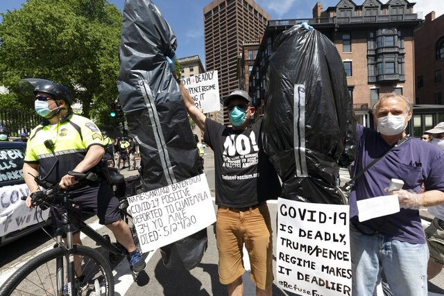 A counter-demonstrator holds up makeshift body bags while separated by police from a protest calling for the repeal of all government restrictions related to concern about the spread of COVID-19, Saturday, May 30, 2020, at the Statehouse, in Boston. (AP Photo/Michael Dwyer)