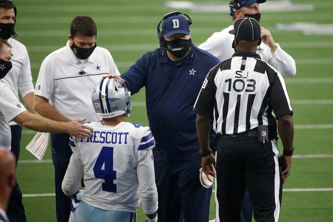 Dallas Cowboys quarterback Dak Prescott (4) is checked on by staff and head coach Mike McCarthy, second from right, who talks with field judge Eugene Hall (103) in the second half of an NFL football game against the Atlanta Falcons in Arlington, Texas, Sunday, Sept. 20, 2020. (AP Photo/Ron Jenkins)