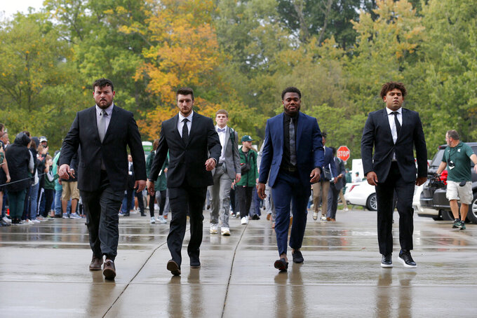 Michigan State players, including, from left to right, Kevin Jarvis, Cody Waddell, Brandon Wright and Connor Heyward, enter Spartan Stadium before an NCAA college football game against Western Kentucky, Saturday, Oct. 2, 2021, in East Lansing, Mich. (AP Photo/Al Goldis)