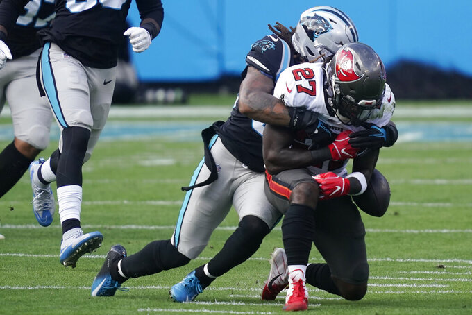 Carolina Panthers outside linebacker Shaq Thompson (54) hits Tampa Bay Buccaneers running back Ronald Jones (27) causing a fumble during the first half of an NFL football game, Sunday, Nov. 15, 2020, in Charlotte , N.C. (AP Photo/Gerry Broome)