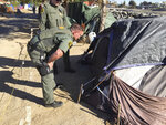 FILE - In this Jan 22, 2018, file photo, Orange County Sheriff's deputies tell people they need to begin he process of packing up along the Santa Ana riverbed in Anaheim, Calif. Homeless residents and their advocates are expected to argue in U.S. court Tuesday, Feb. 13, that Orange County can't remove them from a riverbed bike trail without adequate housing options. Officials say they've offered shelter beds and housing. (Bill Alkofer/The Orange County Register via AP, File)
