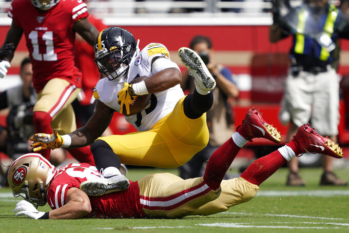 Pittsburgh Steelers linebacker Devin Bush, top, falls over San Francisco 49ers tight end George Kittle after recovering a fumble by 49ers running back Raheem Mostert during the first half of an NFL football game in Santa Clara, Calif., Sunday, Sept. 22, 2019. (AP Photo/Tony Avelar)