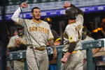 San Diego Padres' Manny Machado, left, congratulates Wil Myers who returns to the dugout after hitting a solo home run off Colorado Rockies starting pitcher German Marquez in the fourth inning of a baseball game Monday, Aug. 31, 2020, in Denver. (AP Photo/David Zalubowski)