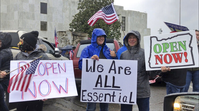 FILE - In this May 2, 2020, file photo, people hold signs protesting Oregon Gov. Kate Brown's executive order that shut down much of the state's economy and imposed social distancing, in her effort to stem the spread of the coronavirus, rally outside the Oregon State Capitol in Salem, Ore. A judge in rural Oregon on Monday, May 18, tossed out statewide coronavirus restrictions imposed by Brown, saying she didn't seek the Legislature's approval to extend the stay-at-home orders beyond a 28-day limit. (AP Photo/Andrew Selsky, File)