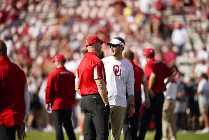 Nebraska head coach Scott Frost, left, talks with Oklahoma head coach Lincoln Riley, right, before an NCAA college football game, Saturday, Sept. 18, 2021, in Norman, Okla. (AP Photo/Sue Ogrocki)