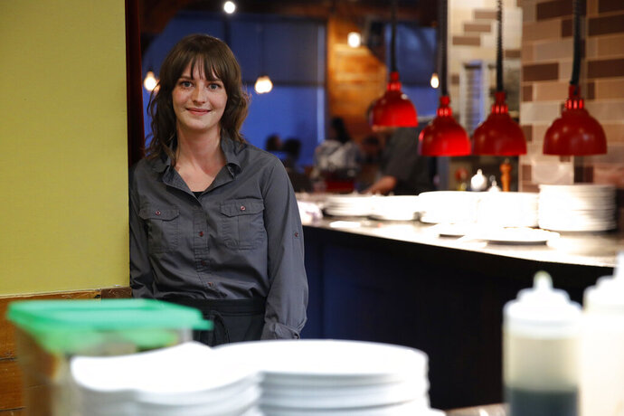 In this Jan. 18, 2020, restaurant server Chloe Sokolov poses for a photo while working at Eatery A in Des Moines, Iowa. Though Sokolov always considered herself a supporter of Democratic presidential candidate Sen. Bernie Sanders, I-Vt., she plans to caucus for the first time this year in part because Sanders' campaign convened more than 50 service industry workers to discuss their economic challenges. (AP Photo/Patrick Semansky)