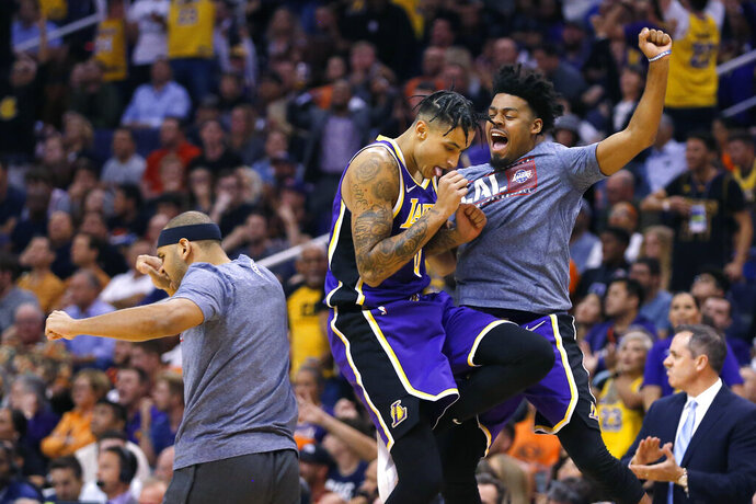 Los Angeles Lakers forward Kyle Kuzma (0) celebrates with teammates after defeating the Phoenix Suns 123-115 during an NBA basketball game, Tuesday, Nov. 12, 2019, in Phoenix. (AP Photo/Rick Scuteri)