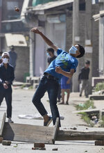 A Kashmiri protester throws stones on government forces while marching on the streets in solidarity with rebels engaged in a gunbattle with soldiers, in Srinagar, Indian controlled Kashmir, Thursday, Sept. 17, 2020. The gunfight erupted shortly after scores of counterinsurgency police and soldiers launched an operation based on a tip about the presence of militants in a Srinagar neighborhood, Pankaj Singh, an Indian paramilitary spokesman, said. (AP Photo/Mukhtar Khan)