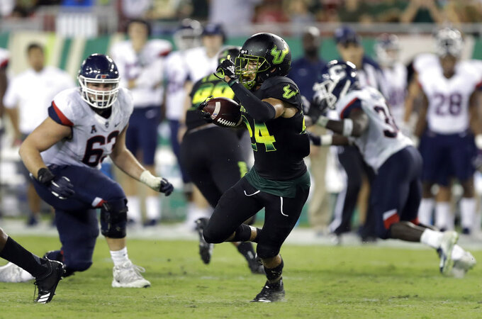 South Florida defensive back Nick Roberts (24) runs with the ball after intercepting a pass by Connecticut quarterback David Pindell during the second half of an NCAA college football game Saturday, Oct. 20, 2018, in Tampa, Fla. (AP Photo/Chris O'Meara)