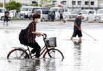 A man on a bicycle makes his way through a flooded road following heavy rains in Kurume, Fukuoka prefecture, southern Japan Wednesday, July 8, 2020. Floodwaters flowed down streets in southern Japanese towns hit by heavy rains. (Shoei Miyano/Kyodo News via AP)