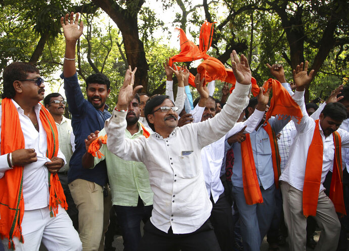 Bharatiya Janata Party (BJP) supporters dance to celebrate after their leader B. S. Yeddyurappa was sworn in as Chief Minister of Karnataka state in Bangalore, India, Thursday, May 17, 2018. The elections in India's southern state of Karnataka were held on last Saturday. (AP Photo/Aijaz Rahi)