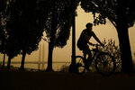 A person rides a bike along the Willamette River as smoke from wildfires partially obscures the Tilikum Crossing Bridge, Saturday, Sept. 12, 2020, in Portland, Ore. (AP Photo/John Locher)