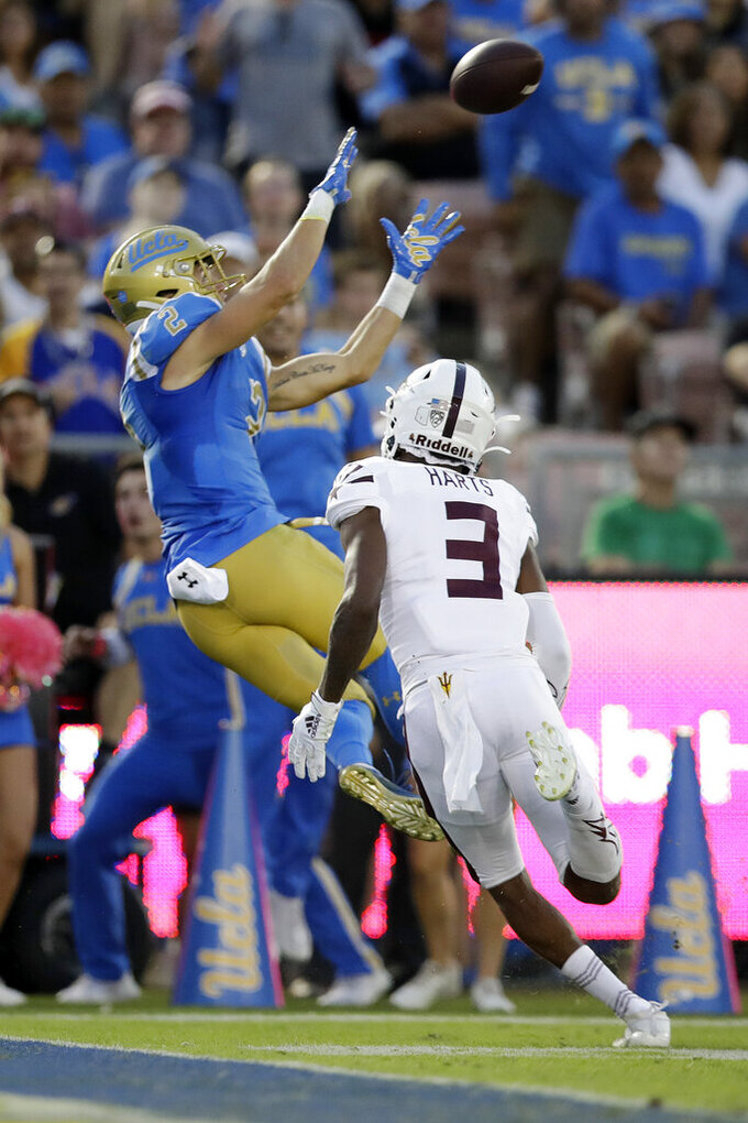 UCLA wide receiver Kyle Philips, left, catches a touchdown in front of Arizona State defensive back Willie Harts (3) during the first half of an NCAA college football game Saturday, Oct. 26, 2019, in Pasadena, Calif. (AP Photo/Marcio Jose Sanchez)