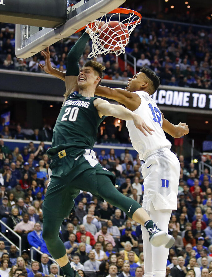 Michigan State guard Matt McQuaid (20) scores against Duke forward Javin DeLaurier (12) during the first half of an NCAA men's East Regional final college basketball game in Washington, Sunday, March 31, 2019. (AP Photo/Alex Brandon)