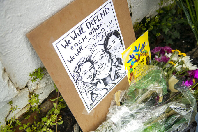 Flowers, candles and signs are displayed at a makeshift memorial outside of the Gold Spa in Atlanta, Wednesday, March 17, 2021. According to authorities, three Asian women were found dead inside of the Gold Spa on Tuesday night and another Asian woman was found dead at Aromatherapy Spa across the street. Police in the Atlanta suburb of Gwinnett County say they've begun extra patrols in and around Asian businesses there following the shooting at three massage parlors in the area that killed eight, most of them women of Asian descent. (Alyssa Pointer/Atlanta Journal-Constitution via AP)