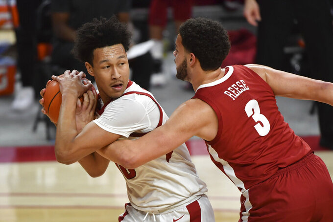 Arkansas forward Jaylin Williams tries to keep the ball from Alabama forward Alex Reese (3) during the second half of an NCAA college basketball game in Fayetteville, Ark., Wednesday, Feb. 24, 2021. (AP Photo/Michael Woods)