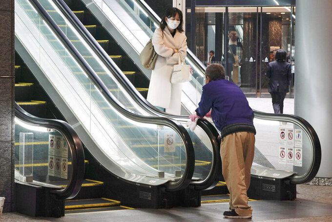 A woman wearing a mask as a precaution against a new coronavirus passes by a worker cleaning escalator handrails at a business building in Tokyo Monday, March 9, 2020. (AP Photo/Eugene Hoshiko)