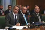 Greek Prime Ministers Kyriakos Mitsotakis, left, speaks next to Finance Minister Christos Staikouras, center, and Greek Foreign Minister Nikos Dendias as the new government participate in their first cabinet meeting, in Athens, Wednesday, July 10, 2019. Conservative party leader Kyriakos Mitsotakis won Sunday's election on pledges that included making the country more businesses-friendly, cutting taxes and negotiating an easing of draconian budget conditions agreed as part of the country's rescue program. (AP Photo/Petros Giannakouris)