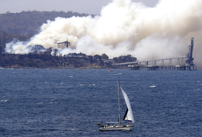 A yacht sails past a burning woodchip mill as the wildfires hits the town of Eden, New South Wales, Australia, Friday, Jan. 10, 2020. The wildfires have destroyed more than 2,000 homes and continue to burn, threatening to flare up again as temperatures rise. (AP Photo/Rick Rycroft)