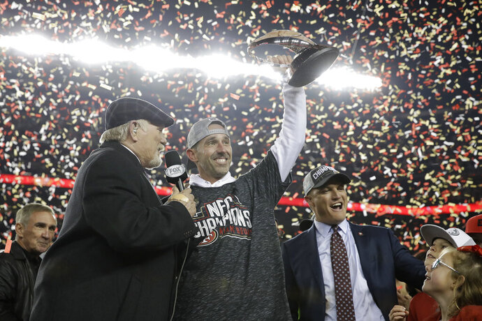 San Francisco 49ers head coach Kyle Shanahan, center, and general manager John Lynch, right, celebrate while interviewed by Terry Bradshaw after the NFL NFC Championship football game against the Green Bay Packers Sunday, Jan. 19, 2020, in Santa Clara, Calif. The 49ers won 37-20 to advance to Super Bowl 54 against the Kansas City Chiefs. Also pictured at bottom left is Mike Shanahan. (AP Photo/Marcio Jose Sanchez)