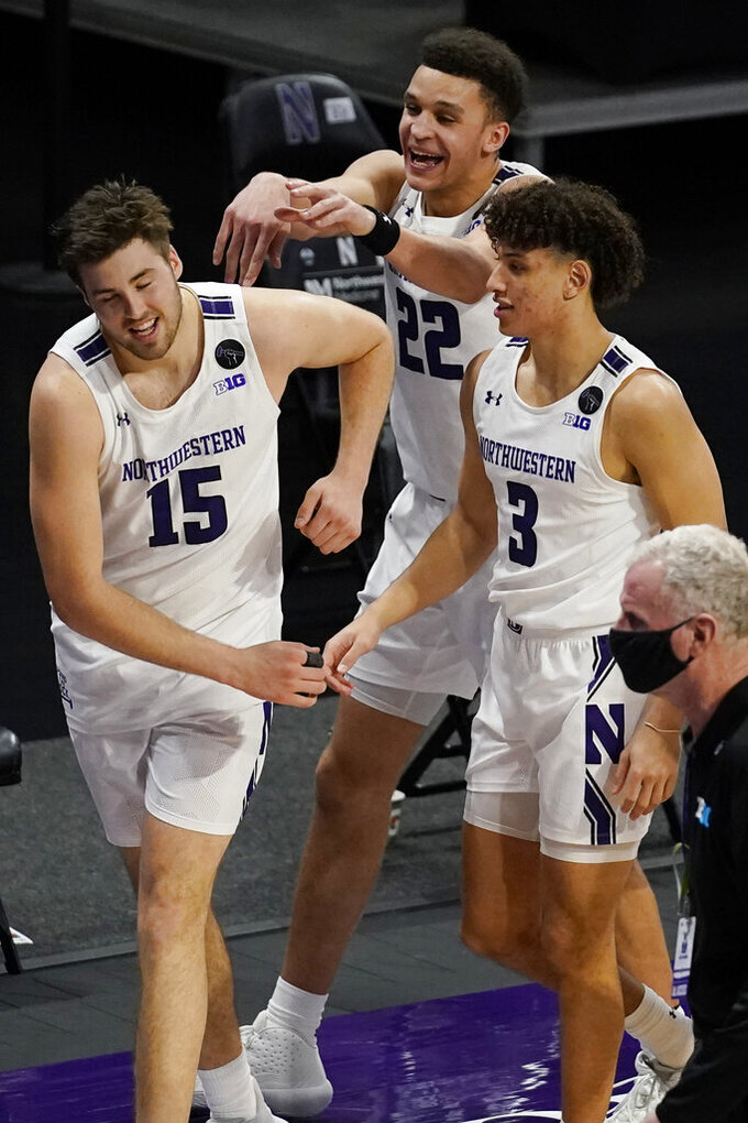 Northwestern forward Pete Nance, center, celebrates with center Ryan Young and guard Ty Berry after Northwestern defeated Maryland 60-55 in an NCAA college basketball game in Evanston, Ill., Wednesday, March 3, 2021. (AP Photo/Nam Y. Huh)