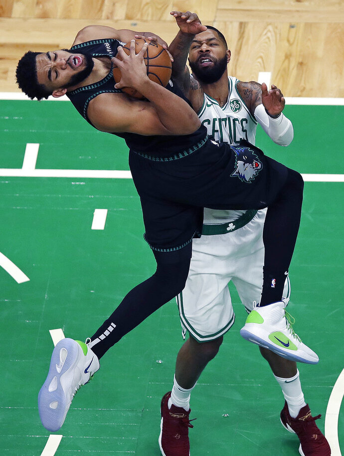 Minnesota Timberwolves center Karl-Anthony Towns, left, is fouled by Boston Celtics forward Marcus Morris on a drive to the basket during the third quarter of an NBA basketball game in Boston, Wednesday, Jan. 2, 2019. (AP Photo/Charles Krupa)