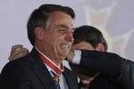 Brazil's President Jair Bolsonaro receives the Maua Merit Medal for services to the national infrastructure, in Brasilia, Brazil, Thursday, Aug. 15, 2019.  (AP Photo/Eraldo Peres)