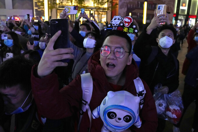 Supporters of the 2022 Beijing Winter Olympics cheer as they mark the start of the 100 days countdown to the opening of the Winter Olympics in Beijing, China, Tuesday, Oct. 26, 2021. (AP Photo/Ng Han Guan)