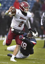 Massachusetts quarterback Ross Comis (2) shakes a tackle by Connecticut linebacker Kevon Jones (48) during the first half of an NCAA college football game, Saturday, Oct. 27, 2018, in East Hartford, Conn. (AP Photo/Jessica Hill)