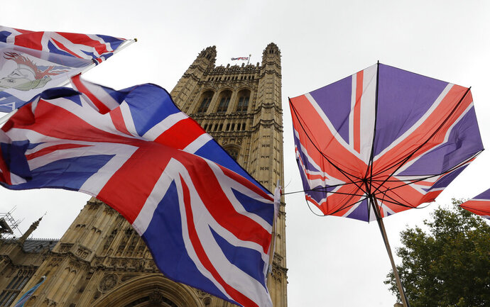 Union flags and an umbrella tied to railings in front of Parliament in London, Friday, Oct. 25, 2019. Politicians in Britain and the European Union seem to be looking to each other to break the Brexit deadlock. (AP Photo/Kirsty Wigglesworth)