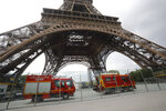 Rescue workers vehicles park just down the Eiffel Tower Monday, May 20, 2019 in Paris. The Eiffel Tower has been closed to visitors after a person has tried to scale it. (AP Photo/Michel Euler)