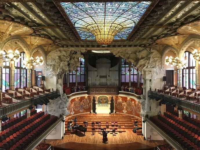This Oct. 14, 2019 photo shows the inside of Palau de la Música Catalana, built by famed architect Lluís Domènech I Montaner,  in Barcelona, Spain. A required tour of the music hall's crescendo of colorful stained glass and mosaics is pricey but worth it, and you may even catch musicians practicing. (Courtney Bonnell via AP)