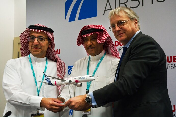 Flynas CEO Bander al-Mohanna, left, flynas chairman Ayed Thawab al-Jeaid, center, and Airbus' chief commercial officer Christian Scherer pose during a news conference at the Dubai Airshow in Dubai, United Arab Emirates, Tuesday, Nov. 19, 2019. Saudi budget carrier flynas announced a firm order Tuesday of 10 Airbus A321XLR, a deal valued at $1.4 billion at list price. (AP Photo/Jon Gambrell)