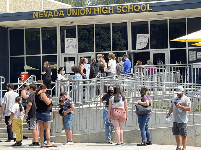 FILE - Nevada Union High School students, parents, and families wait in line to show proof of having been vaccinated for COVID-19, or to get tested for the virus in Grass Valley, Calif., on Saturday, Aug. 21, 2021. In most states, minors need the consent of their parents in order to be vaccinated against COVID-19. Navigating family politics in cases of differing views has been a challenge for students and organizers of outreach campaigns, who have faced blowback for directly targeting young people. (Elias Funez/The Union via AP, File)