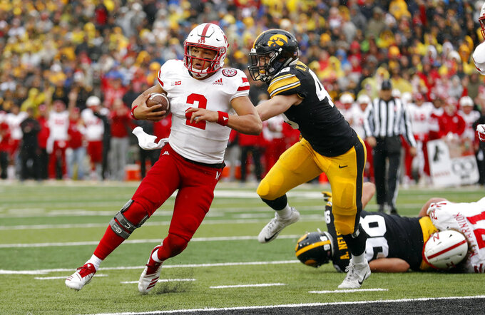 Nebraska quarterback Adrian Martinez (2) runs from Iowa linebacker Nick Niemann during a 3-yard touchdown in the second half of an NCAA college football game, Friday, Nov. 23, 2018, in Iowa City, Iowa. Iowa won 31-28. (AP Photo/Charlie Neibergall)