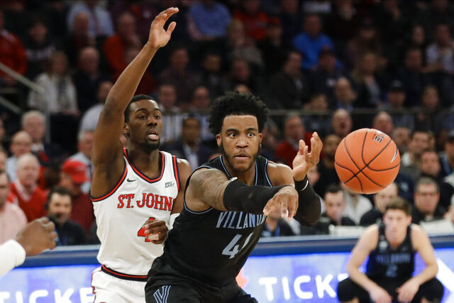 Villanova's Saddiq Bey (41) passes the ball away from St. John's Greg Williams Jr. (4) during the first half of an NCAA college basketball game Tuesday, Jan. 28, 2020, in New York. (AP Photo/Frank Franklin II)