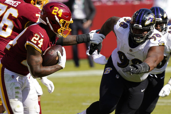 Washington Football Team running back Antonio Gibson (24) runs against Baltimore Ravens defensive tackle Brandon Williams (98) during the second half of an NFL football game, Sunday, Oct. 4, 2020, in Landover, Md. (AP Photo/Steve Helber)