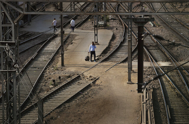 In this Monday, March 23, 2020, photo, a passenger walks past railway tracks at the deserted New Delhi Railway station during a lockdown amid concerns over the spread of Coronavirus, in New Delhi, India, Monday. India's colossal passenger railway system has come to a halt as officials take emergency measures to keep the coronavirus pandemic from spreading in the country of 1.3 billion. The railway system is often described as India's lifeline, transporting 23 million people across the vast subcontinent each day, some 8.4 billion passengers each year. (AP Photo/Manish Swarup)