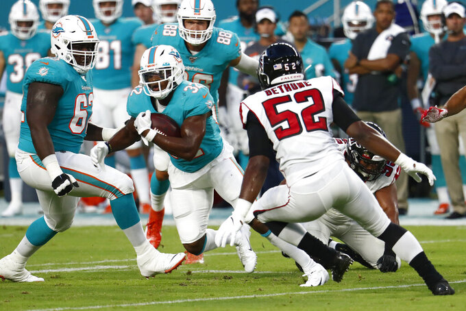 Miami Dolphins running back Kenyan Drake (32) runs as Atlanta Falcons linebacker Yurik Bethune (52) defends during the first half of a preseason NFL football game Thursday, Aug. 8, 2019, in Miami Gardens, Fla. (AP Photo/Brynn Anderson)