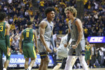 West Virginia guard Miles McBride (4) and forward Emmitt Matthews Jr. (11) celebrate after a score against Baylor during the second half of an NCAA college basketball game Saturday, March 7, 2020, in Morgantown, W.Va. (AP Photo/Kathleen Batten)