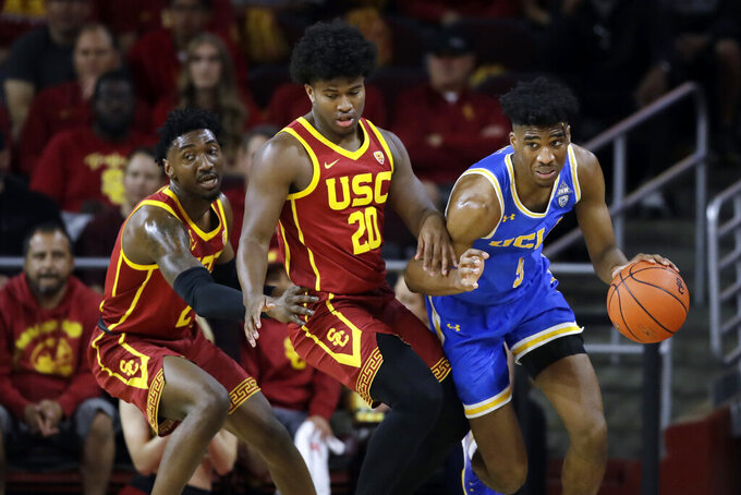 UCLA guard Chris Smith, right, is defended by Southern California guard Ethan Anderson (20) and guard Jonah Mathews during the first half of an NCAA college basketball game Saturday, March 7, 2020, in Los Angeles. (AP Photo/Marcio Jose Sanchez)
