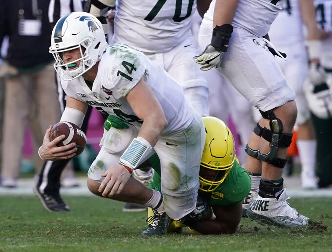 Michigan State quarterback Brian Lewerke (14) is sacked by Oregon linebacker Justin Hollins (11) during the second half of the Redbox Bowl NCAA college football game Monday, Dec. 31, 2018, in Santa Clara, Calif. (AP Photo/Tony Avelar)