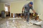 Joe Miles, right, and Rey Varea, left, cut out drywall to prevent mold the day after severe weather flooded the home in the Broadmoor neighborhood in New Orleans, Thursday, July 11, 2019.  (Max Becherer/The Advocate via AP)