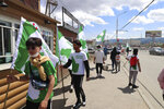 Election workers and supporters of Mongolian Green Party wearing green and white t-shirt campaign in the Chingeltei district, northern outskirt of Ulaanbaatar, Mongolia, Monday, June 22, 2020. Mongolia holds parliamentary elections on Wednesday, continuing a nearly 30-year democratic system in a vast but lightly populated country sandwiched between authoritarian regimes in Russia and China and beset by economic problems. (AP Photo/Ganbat Namjilsangarav)