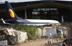 A man stands next to his shanty as Jet Airways aircraft is seen parked at a hanger at Chhatrapati Shivaji Maharaj International Airport in Mumbai, Monday, March 25, 2019. The chairman of India's private Jet Airways has quit amid mounting financial woes forcing the airline to suspend operations on 14 international routes with more than 80 planes grounded. (AP Photo/Rafiq Maqbool)