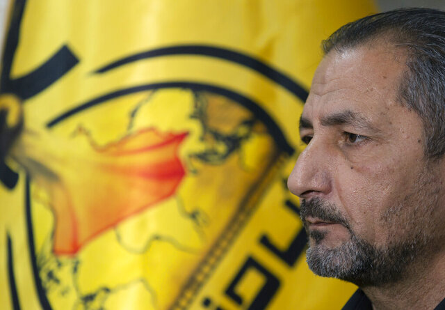 Mohammed Mohieh, the spokesman of Iraq's Iranian-backed Kataeb Hezbollah, or Hezbollah Brigades, gives an interview at his office, in Baghdad, Iraq, Monday, Dec. 30, 2019. Mohieh said Monday that the death toll from U.S. military strikes in Iraq and Syria against its fighters has risen to 25, vowing to exact revenge for the