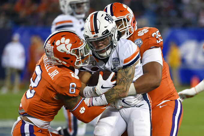 Clemson cornerback A.J. Terrell (8) and defensive end Justin Foster (35) tackle Virginia running back Billy Kemp IV (80) during the first half of the Atlantic Coast Conference championship NCAA college football game in Charlotte, N.C., Saturday, Dec. 7, 2019. (AP Photo/Mike McCarn)