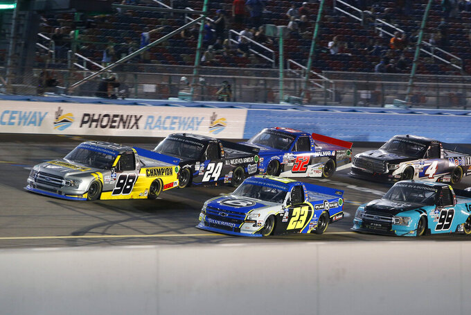 Grant Enfinger (98) and Brett Moffitt (23) lead the field for a restart during the NASCAR Truck Series auto race at Phoenix Raceway, Friday, Nov. 6, 2020, in Avondale, Ariz. (AP Photo/Ralph Freso)